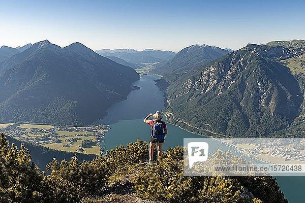 Junge Wanderin  Frau blickt in die Ferne  Blick vom Berg Bärenkopf auf den Achensee  links Seebergspitze und Seekarspitze  rechts Rofangebirge  Tirol  Österreich  Europa
