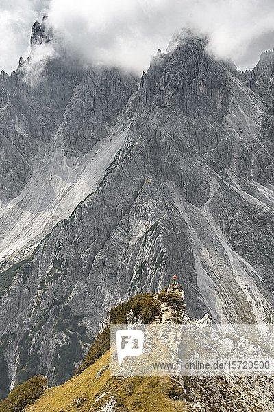 Bergsteigerin  Frau steht auf einem Grat und blickt in ein Kar  dramatische Wolken  hinten Felswände des Cimon di Croda Liscia  Auronzo di Cadore  Belluno  Italien  Europa