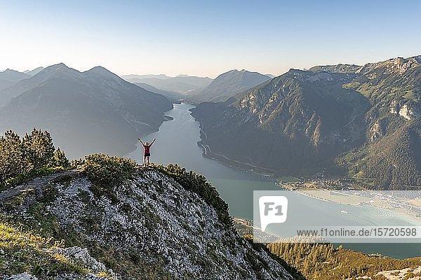 Junge Frau streckt Arme in die Luft  Ausblick vom Berg Bärenkopf auf den Achensee  links Seebergspitze und Seekarspitze  rechts Rofangebirge  Tirol  Österreich  Europa