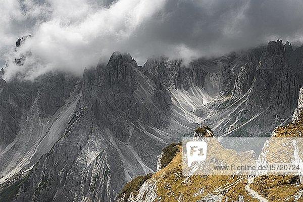 Frau in roter Jacke steht auf einem Grat  hinten Berggipfel und spitzige Felsen  dramatische Wolken  Cimon di Croda Liscia und Cadini-Gruppe  Auronzo di Cadore  Belluno  Italien  Europa