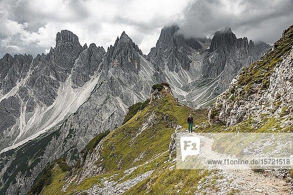 Junge Frau  Bergsteigerin auf einem Wanderweg  hinten Berggipfel und spitze Felszacken  dramatische Wolken  Cimon di Croda Liscia und Cadini-Gruppe  Sextener Dolomiten  Belluno  Italien  Europa