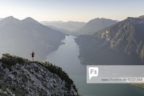 Junge Frau blickt über Berglandschaft  Ausblick vom Berg Bärenkopf auf den Achensee  links Seebergspitze und Seekarspitze  rechts Rofangebirge  Tirol  Österreich  Europa