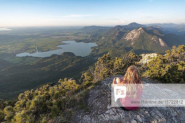 Junge Frau sitzt am Gipfel  Ausblick vom Herzogstand auf Kochelsee  Jochberg und Alpenvorland  Alpen  Oberbayern  Bayern  Deutschland  Europa