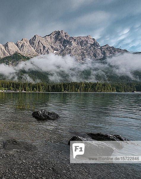 Felsen am Ufer  Eibsee vor Zugspitzmassiv mit Zugspitze  tief hängende Wolken  Wettersteingebirge  bei Grainau  Oberbayern  Bayern  Deutschland  Europa