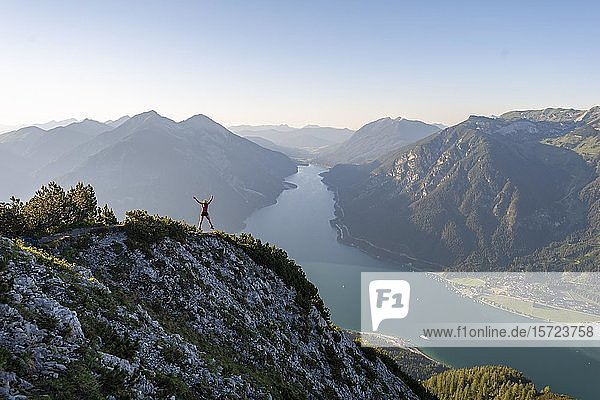 Junge Frau springt in die Luft,  Ausblick vom Berg Bärenkopf auf den Achensee,  links Seebergspitze und Seekarspitze,  rechts Rofangebirge,  Tirol,  Österreich,  Europa
