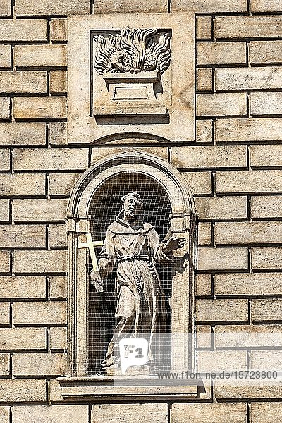 Statue of St. Francis of Assisi in a niche on the facade of the Church of the Knights of the Cross  Old Town  Prague