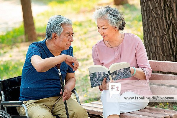 The elderly couple sitting in the park reading a book