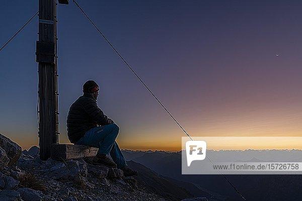 Sonnenaufgang über Lechtaler Alpen mit Bergsteiger und Gipfelkreuz Ellbogener Spitze  Elbigenalp  Lechtal  Außerfern  Tirol  Österreich  Europa