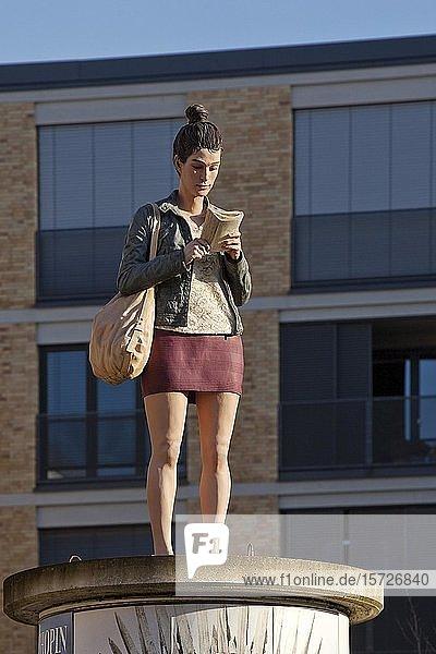 Skulptur Säulenheilige Lesende auf einer Litfaßsäule  Künstler Christoph Pöggeler  Düsseldorf  Nordrhein-Westfalen  Deutschland  Europa