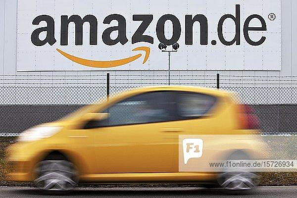 Gelber fahrender Pkw vor Amazon Logistikzentrum  Rheinberg  Nordrhein-Westfalen  Deutschland  Europa