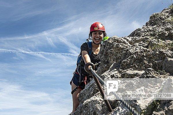 Lachende junge Frau mit Kletterhelm und an mit Seil gesichertem Fels  Bergsteigerin an einem Klettersteig  Mittenwalder Höhenweg  Karwendelgebirge  Mittenwald  Deutschland  Europa