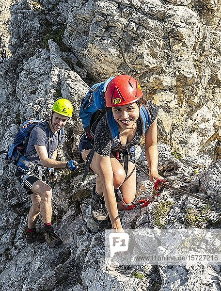 Two mountaineers  pair  with helmet on a secured fixed rope route  Mittenwald via ferrata  Karwendel Mountains  Mittenwald  Germany  Europe