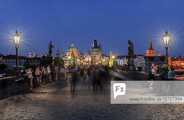 Karl?v most  Menschen auf der Karlsbrücke bei Abenddämmerung  hinten Kuppel der Kreuzherrenkirche mit Altstädter Brückenturm  Prag  Böhmen  Tschechien  Europa