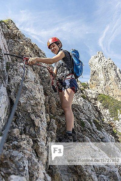 Bergsteigerin  junge Frau mit Helm an einem gesicherten Klettersteig  Mittenwalder Höhenweg  Karwendelgebirge  Mittenwald  Deutschland  Europa