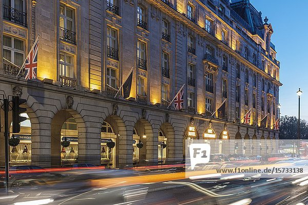 Busy early evening traffic on Piccadilly at the Ritz Hotel London England.