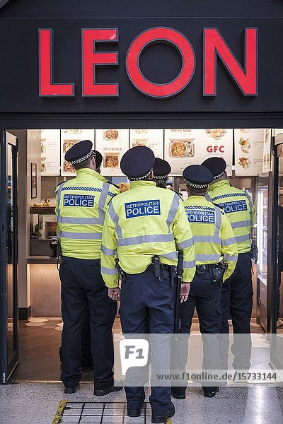 London  UK. Metropolitan police officers stand on queue at fast food restaurant on their lunch break.