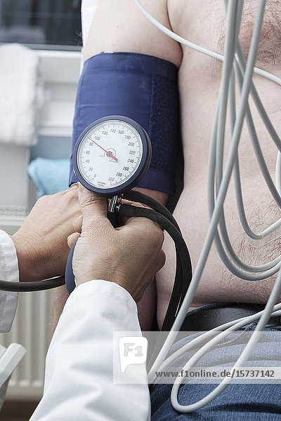 Cardiollogist monitors blood pressure of patient during cardiology strees test.