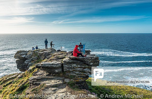 Photographers at Tintagel waiting for the sunset on the Cornish coast. Cornwall  England  UK.