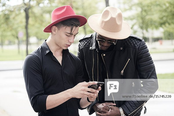 Two men looking at phone. Munich  Germany.