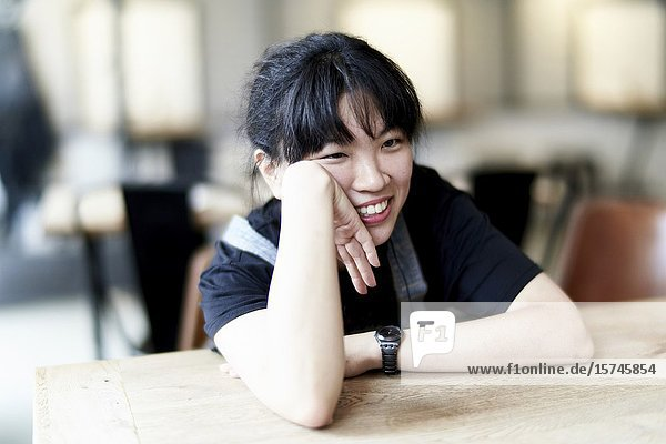 Korean woman sitting at table in cafe  leaning on table  listening.