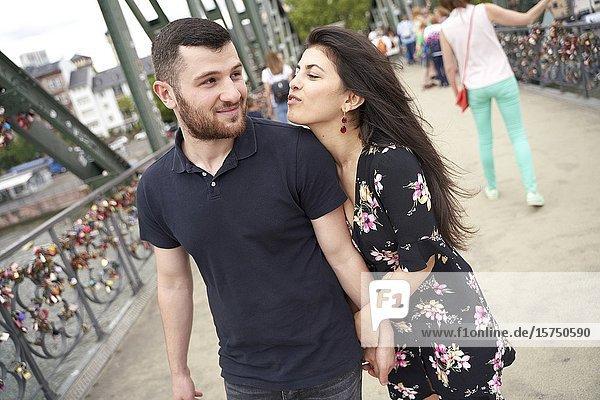 Young couple walking on bridge. Eisener Steg  Frankfurt am Main  Germany.