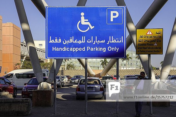 Cairo  Egypt A man stands under a handicapped parking sign at the Cairo Airport parking lot.