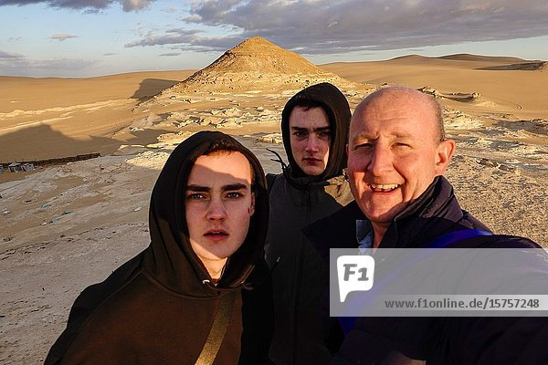 Siwa Oasis  Egypt A father and his sons take a selfie on the sand dunes outside the oasis at sunset.