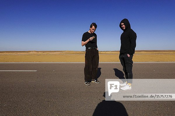 Marsa Matrouh  Egypt Two young men standing on a desert road.