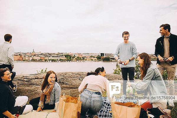 Fröhliche Freunde genießen am See beim Picknick am Wochenende