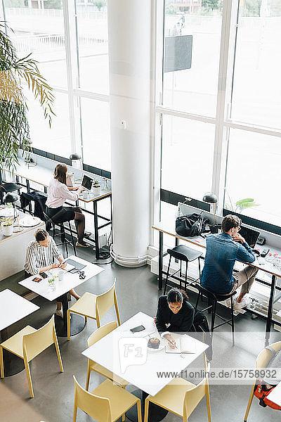Hochwinkelansicht von Geschäftsleuten  die am Schreibtisch im Coworking Space arbeiten