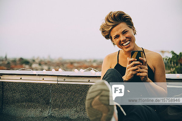 Portrait of cheerful woman using mobile phone while sitting on terrace against sky
