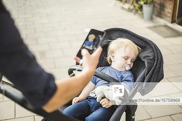 Hand des Vaters fotografiert schlafenden Sohn auf Kinderwagen in der Stadt