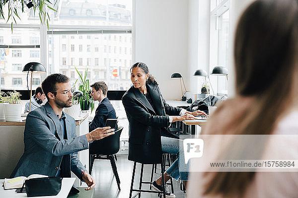 Geschäftsmann zeigt einer Kollegin bei der Arbeit im Coworking Space ein Smartphone