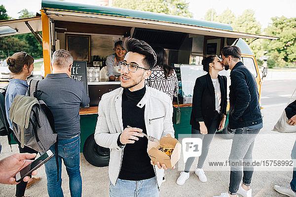Männlicher Kunde mit Kiste  der sich mit einem Freund unterhält  während er gegen einen Speisewagen steht
