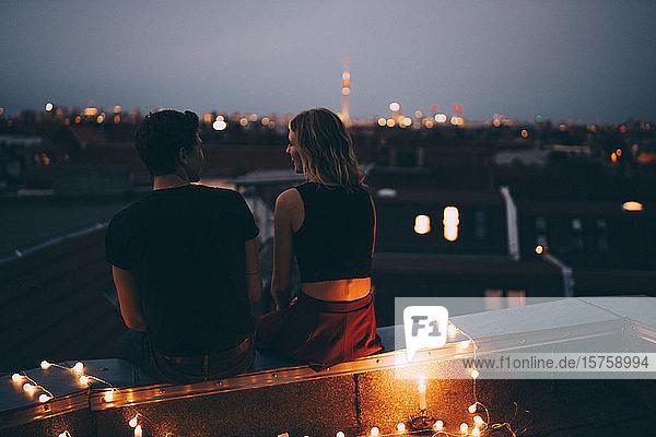 Rückansicht eines jungen Paares  das in der Abenddämmerung auf einer beleuchteten Terrasse in der Stadt sitzt