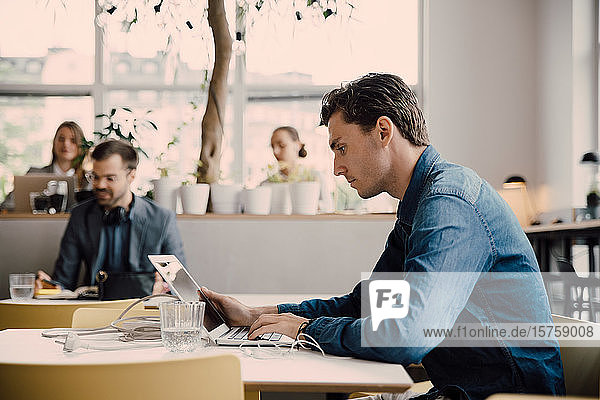 Side view of young businessman using laptop while sitting at desk in coworking space