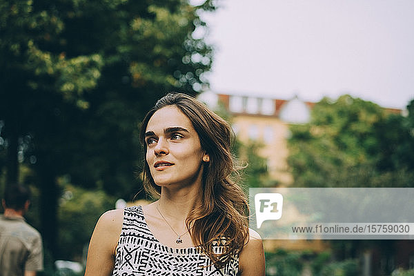 Thoughtful smiling young woman looking away in city