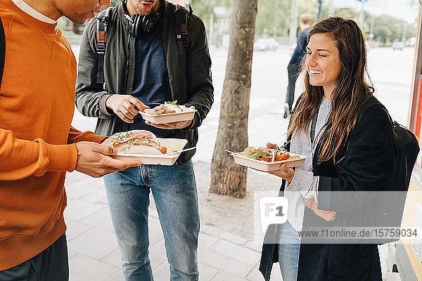 Lächelnde junge Frau genießt Essen mit männlichen Freunden  während sie mit einem Speisewagen auf der Straße steht