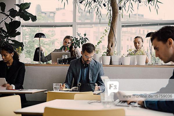 Männliche und weibliche Angestellte  die am Schreibtisch im Coworking Space arbeiten