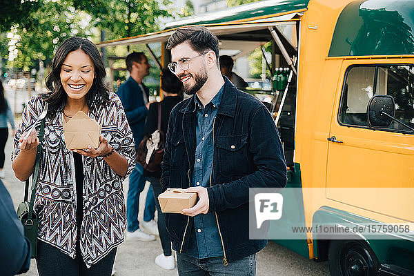 Female laughing while standing by male friend with box against food truck