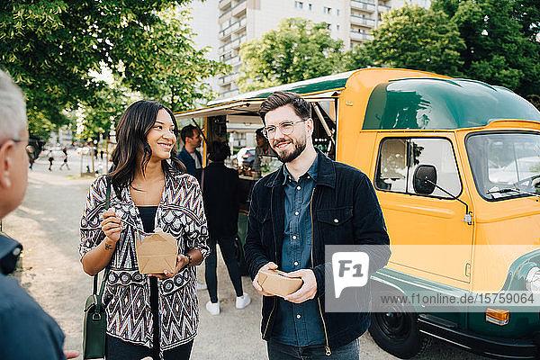 Lächelnder Freund und Freundin mit Kiste  die gegen einen Speisewagen stehen