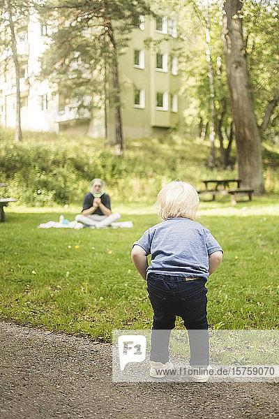 Rückansicht in voller Länge eines auf einem Fußweg stehenden Jungen mit einem im Park sitzenden Vater