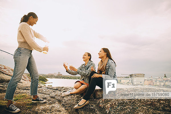 Woman giving drink to friends on rock formation at lakeshore against sky