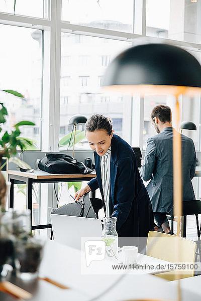Geschäftsfrau prüft Akte  während sie an einem Schreibtisch in der Cafeteria steht