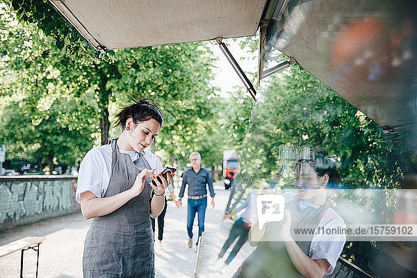 Female young owner using smart phone while standing by food truck
