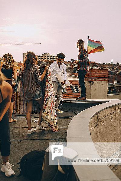 Freunde arrangieren Decke auf der Terrasse für eine Dachparty in der Stadt