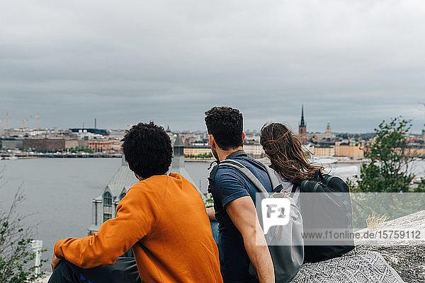 Rückansicht von Freunden  die auf einem Hügel am Fluss in der Stadt gegen den Himmel sitzen