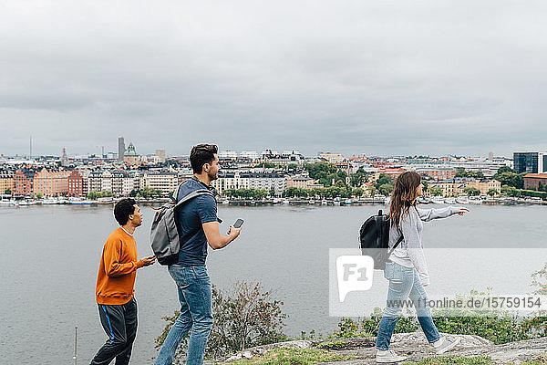 Freunde in voller Länge zu Fuß am Fluss in der Stadt gegen den Himmel