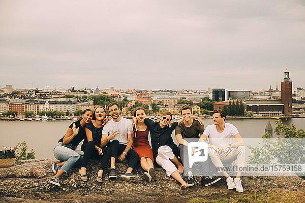Glückliche Freunde sitzen in voller Länge auf einer Felsformation gegen die Stadt