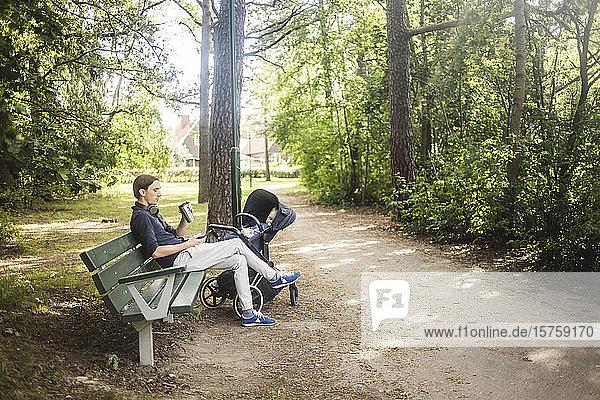 Ein Mann in voller Länge benutzt ein Smartphone  während er neben einem Baby sitzt  das im Kinderwagen im Park schläft